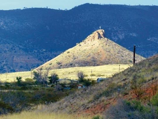 The cross on Round Mountain west of Mescalero and Bent catches the sunlight.