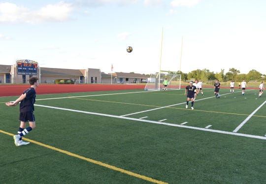 A South Lyon Lion tosses in the ball from the sidelines on Aug. 27.