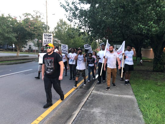 Protesters march Tuesday to the Pensacola Police Department to call for the firing of the officers involved in the shooting death of Tymar Crawford.