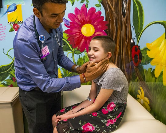 Dr. Naresh Reddivalla, hematologist and oncologist, examines Peyton Gonzales, 9, at Cardon Children's Medical Center in Mesa, Tuesday, August 27, 2019. Peyton has been battling a very rare form of cancer.