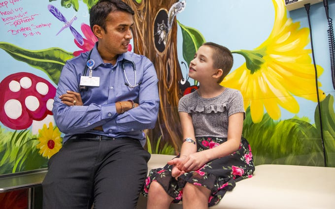 Dr. Naresh Reddivalla, hematologist and oncologist, speaks with Peyton Gonzales, 9, at Cardon Children's Medical Center in Mesa, Tuesday, August 27, 2019. Peyton has been battling a very rare form of cancer.