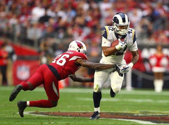 Cardinals cornerback Brandon Williams tries to tackle Rams running back John Kelly (42) during a game Dec 23 at State Farm Stadium.