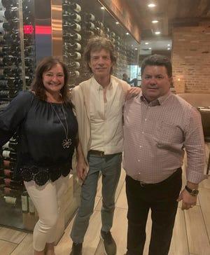 Paula and Fernando Esteves surround Mick Jagger at Spiga Cucina Italiana on Tuesday, Aug. 27.