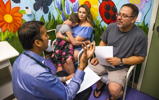 Dr. Naresh Reddivalla, hematologist and oncologist, left, explains cancer treatment results to Jake Gonzales, right, father of Peyton Gonzales, 9, at Cardon Children's Medical Center in Mesa, Tuesday, August 27, 2019. Peyton has been battling a very rare form of cancer and is now cancer-free. Peyton is held by her mother, Brittany Van Eynde.