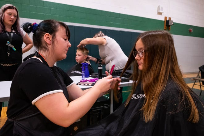 Madison Sheridan, a sixth-grader at Holland Woods Middle School, has her hair cut by Kennedy Morrow during the school's orientation Wednesday, Aug. 28, 2019.