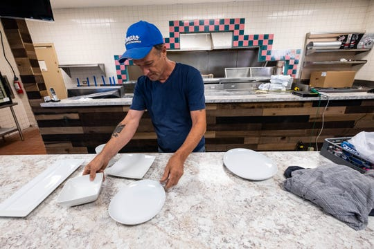 Pete Cubi, owner of Ocean Breeze in Marysville, sets dishware on the front counter of the restaurant Wednesday, Aug. 28, 2019. Cubi owns the restaurant with his wife, Spresa, and son Chris.