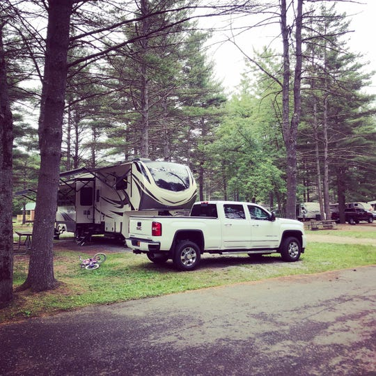 Andrew and Heather Nikola's 2019 Grand Designs Solitude Fifth Wheel is parked in a campground. A fifth-wheel is designed to be towed by a pickup truck equipped with a device known as a fifth-wheel hitch.