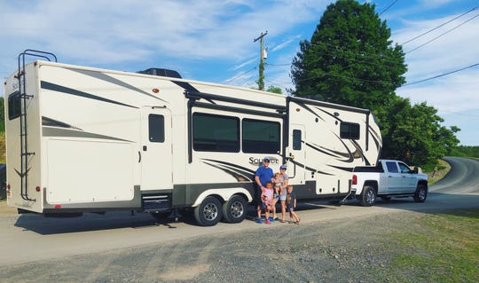 Andrew and Heather Nikola and their children, Sophia, Jameson and Brayden, stand next to their 2019 Grand Design Solitude Fifth Wheel, on their property in Marlboro.