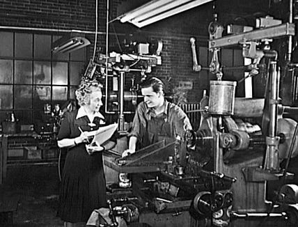You could say that Floorola shifted from waxing floors to scrubbing Axis foes. Kay Busser is seen with an employee at the former maker of floor waxers.