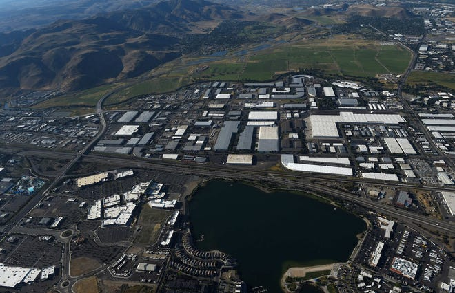 The Tesla Gigafactory 1, the Tahoe Reno Industrial Center, Reno, Sparks and the Reno-Tahoe International Airport are seen from the air on Aug. 24, 2019.