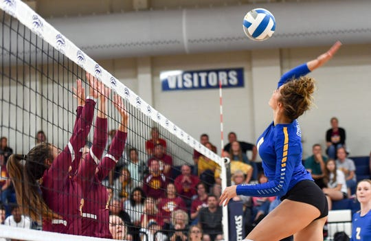 Sydney Wambach of The O'Gorman Knights hits the ball past the fingertips of two Roosevelt Rough Riders in a volleyball match Tuesday night, August 27, at O'Gorman High School in Sioux Falls.