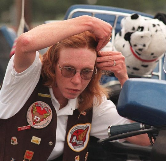 Diane DeLuca, of Columbus, Ohio, fixes her hair using the rearview mirror on her Goldwing motorcycle after arriving at the Wingding in 1999.