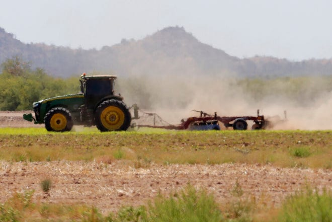 Intense heat ripples obscure a farmer turning his field, Tuesday, Aug. 27, 2019 in Casa Blanca, Ariz. Across the Southwest, people are longing for the monsoon rain like a lost summer romance. They're declaring their love online for the seasonal weather pattern that makes the scorching heat somewhat bearable in places like Phoenix and Las Vegas, and helps snuff out wildfires. They're peering out their windows for signs of storm clouds rolling in and calling rain drops a tease. And they're not giving up hope, despite many cities experiencing their driest summers on record. (AP PhotoMatt York)