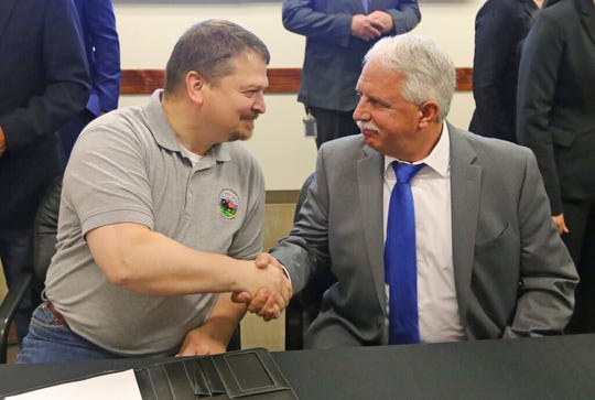 Joseph R. Balash, left, Assistant Secretary for Land and Minerals Management and John Mansanti, President & CEO Crystal Perk Minerals shake hands following the Sevier Playa Potash Project Record of Decision signing Tuesday, Aug. 27, 2019, in Salt Lake City. The Bureau of Land Management has approved a mining project at a lake in central Utah to extract a mineral used in fertilizer that is one of the critical minerals the Trump administration recently said would get streamlined permitting because they are essential to the U.S. economy and security and will help the nation turn away from foreign imports. (AP Photo/Rick Bowmer)