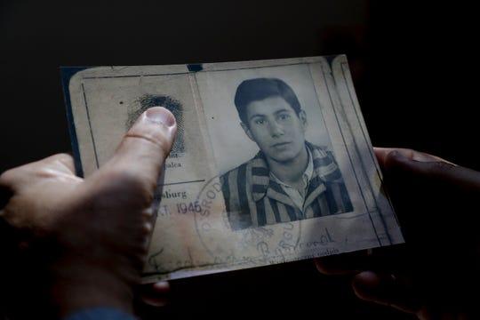 Mark Friedemann holds an identification card that belonged to his father, Richard Friedemann, when he lived through the Holocaust.