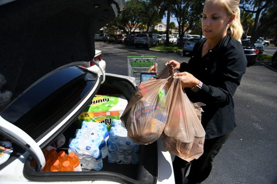 "Kristen Bishop, of Sebastian, picks up extra water, Gatorade, and food at the Publix in The Shoppes of St. Lucie West palza, after work on Wednesday, AUg. 28, 2019, while preparing for the possible arrival of Hurricane Dorian. ""it's important to me to be prepared just in case, this storm is small and has been pretty unpredictable,"" Bishop said. ""I really hope that it stays far away, stays to the east."""