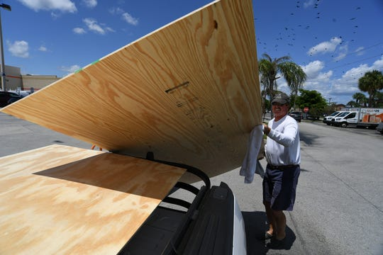 "Brig Burgess, of Palm City, picks up plywood and water while preparing for Hurricane Dorian on Wednesday, Aug. 28, 2019, at Home Depot on U.S. 1 in Stuart. ""I got two doors to cover up and we've been prepared all year. We have our house all ready except for just two doors,"" Burgess said. ""I think you just better be ready for it, you don't know what it's going to do, but we'll figure it out, in about 24 hours we'll know."""