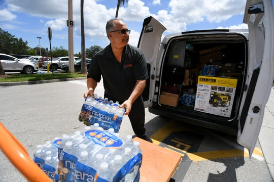 "Danial Acosta, of West Palm Beach, picks up a portable power generator and bottled water at the Home Depot on US 1 in Stuart on Wednesday, Aug. 28, 2019, for his daughter in Palm City in preperationf or Hurricane Dorian. ""You never know, you can never be prepared enough, we've had some pretty good storms here lately,"" Acosta said."