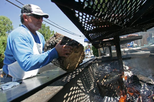 Thousand Oaks Elks Lodge member Lou Reis tosses another piece of oak on the fire during the organization's weekly fundraiser barbecue. The event is open to the public from 10 a.m. to 2 p.m. Saturdays.