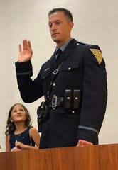 Vineland Police Officer Kevin Vai takes his oath of sergeant as his daughter, Savannah, watches at his side during the City Hall ceremony Aug. 28, 1961