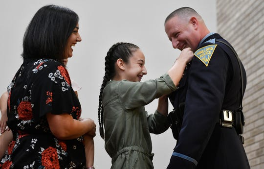 Vineland Police Department Sergeant James Day accepts his new badge, pinned to his jacket by his daughter, Luci.