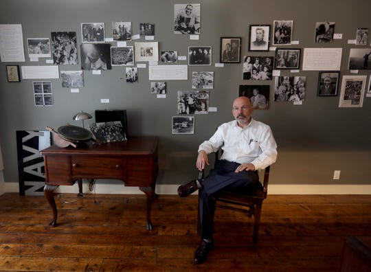 Arne Paglia, founder of the Paul Robeson Gallery in Peekskill, sits in front of a wall of photos of Robeson Aug. 28, 2019. This month marks the 70th anniversary of the Peekskill Race Riots, when protestors who objected to Robeson performing in the area committed acts of violence.