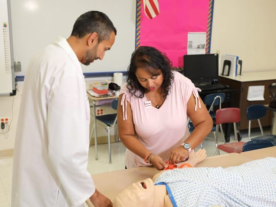 Nisse Varghese, right, a White Plains Middle School teacher works with Dr. Farrukh Jafri, assistant director of education and simulation in the emergency department at White Plains Hospital, to apply a tourniquet at White Plains High School on Wednesday, August 28, 2019.