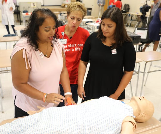 Nisse Varghese, left, a White Plains Middle School teacher and Elizabeth Espada, a speech and language pathologist at Post Rd. Elementary School work with Bernadette Amiducci the director of clinical education at White Plains Hospital, to apply a tourniquet at White Plains High School on Wednesday, August 28, 2019.
