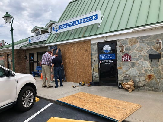 Workers board the front of Sea Cycle Indoor in Lewes off Coastal Highway after a car drove into it Wednesday.