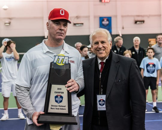 Ohio State coach Ty Tucker (left) holds the 2019 Division I National Men's Tennis Indoor Championship trophy with Jon Vegosen, Chairman of the Board of the Intercollegiate Tennis Association (ITA). The Ty Tucker Tennis Center, named in his honor, will break ground on Friday.