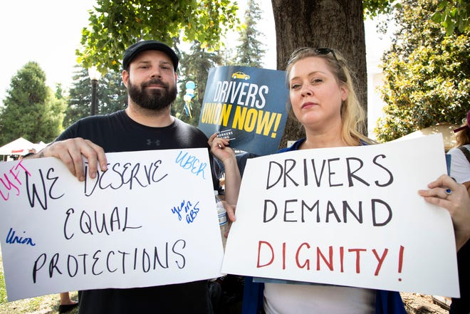 Lyft drivers Danny Raviart and Erica Mighetto hold signs in support of AB 5 on Wednesday, Aug. 28, 2019, in  Sacramento, Calif.