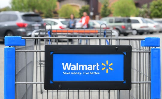 "(FILES) In this file photo taken on May 23, 2019, shoppers carry their goods past a shopping cart in the parking lot of a Walmart Supercenter in Rosemead, California. - Walmart said on June 7, 2019, it was readying a new home delivery service where its employees could come inside and stock up customers' refrigerators. The new ""InHome"" service expected to launch this year in several US cities aims to outdo retail rival Amazon, which brings goods inside customer homes though its electronic access program called Amazon Key. (Photo by Frederic J. BROWN / AFP)FREDERIC J. BROWN/AFP/Getty Images ORIG FILE ID: AFP_1HC23L"