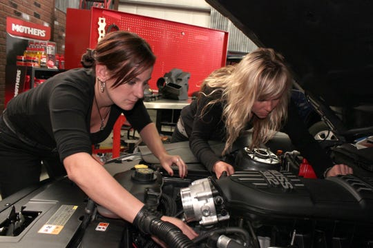 All Girls Garage hosts Bogi, left, and Jessi Combs work on the air intake on an RTR Mustang.