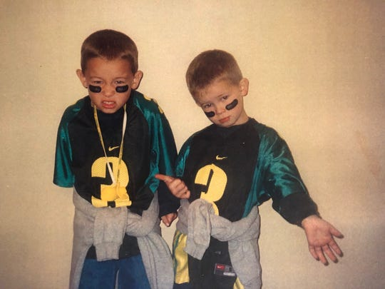 Justin Herbert, right, poses with his older brother Mitchell while wearing the jerseys with the number of former Ducks quarterback Joey Harrington.
