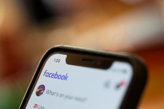 In this Aug. 11, 2019, file photo an iPhone displays a Facebook page in New Orleans. Social media platforms are facing intense, often contradictory demands from Washington to oversee internet content without infringing on First Amendment rights.