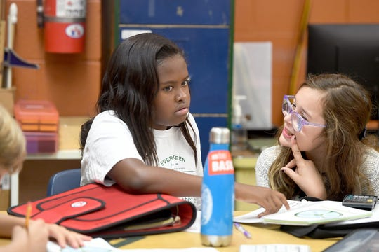 Sixth grade students Akeyla Reed-Kennedy, 11, left, and Nellie Henhoeffer, 11, work on math problems together in their classroom at Evergreen Community Charter School on Aug. 27, 2019.
