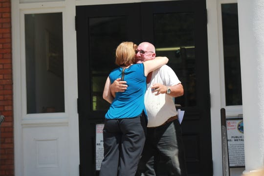 Larry Banks and Laura McIlvane share a hug after both offered personal stories on the impact of substance use on loved ones in their lives.