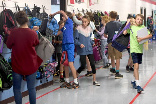 Middle-school children grab their backpacks from hooks in the hallway as they change classes at Evergreen Community Charter School on Aug. 27, 2019.