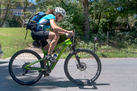 Michele Hobson rides her bike up Michigan Avenue in West Asheville on her lunch break from work on Aug. 29, 2019. Hobson will be competing in the Eco-Challenge, an epic 12-day race through the jungle in Fiji. To compete Hobson, an adventure racer and physical therapist, will bike, paddle, hike, climb, rappel and sail a total of 300 miles. A show about the race will be on Amazon Prime's television streaming service in 2020.