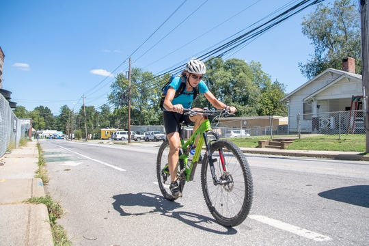 Michele Hobson rides her bike up Haywood Road in West Asheville on her lunch break from work on Aug. 29, 2019. Hobson will be competing in the Eco-Challenge, an epic 12-day race through the jungle in Fiji. To compete Hobson, an adventure racer and physical therapist, will bike, paddle, hike, climb, rappel and sail a total of 300 miles. A show about the race will be on Amazon Prime's television streaming service in 2020.