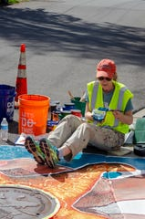 Erica Applewhite works on her starfish mural on Aug. 22. Artists submitted their designs to Kitsap County, and a handful were selected for painting around storm drains in Keyport.