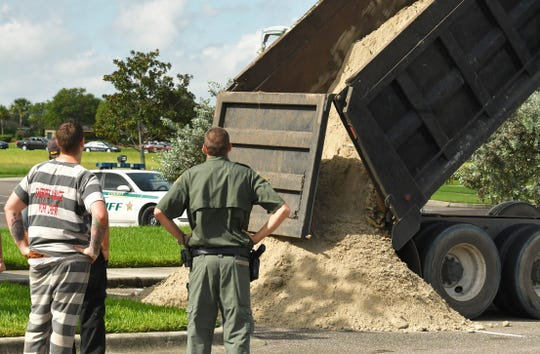 Hundreds of vehicles lined up at 10 a.m. Thursday for free sandbags filled by Brevard County Jail Complex trustees in the parking lot of Calvary Chapel in Viera.