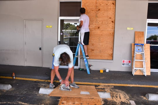 Workers put plywood up on the Showcase Property Management building on Merritt Island, as Brevard County prepares for Hurricane Dorian. The storm may be Category 4 when it arrives on Labor Day.