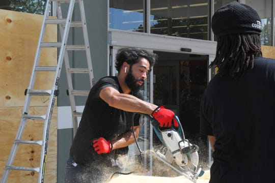 Brevard prepares for the approach of Hurricane Dorian, as crews place plywood on the windows of the Petco store in Viera.