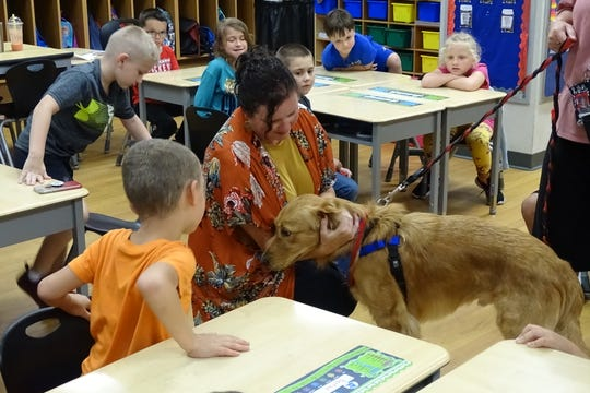 Teacher Kim Makeever greets Rocky during the new school therapy dog's visit to her Bucyrus Elementary School  first-grade classroom on Tuesday.