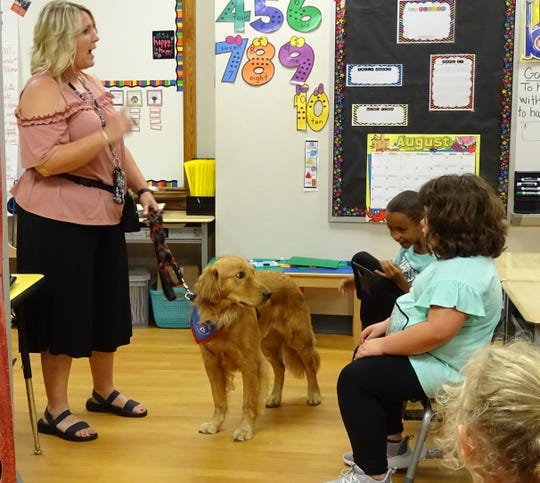 Bucyrus Elementary School counselor Deb  Breidenbach, left, introduces Rocky, a school therapy dog, to Kim Makeever's first-grade class on Tuesday.