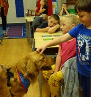 A student in Kim Makeever's first-grade classroom at Bucyrus Elementary School pets Rocky on Tuesday.