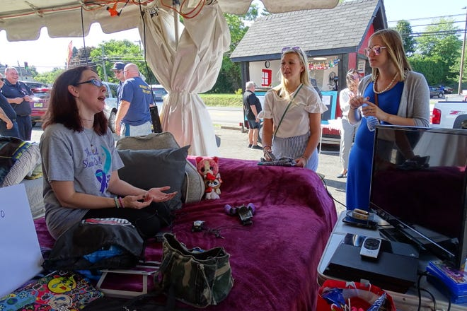 Sarah Lahmon, the Richland County Prosecutor's Office representative in the 2019 Domestic Violence Sleep-Out, speaks with Sharla Akers and Alisha Bazley, from left, of the prosecutor's office as she prepares for the start of the event on Thursday afternoon..