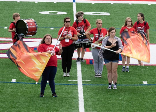 Zane Trace color guards Victoria Rutherford and Lauren Betz practice as the other band members get direction from band director Kate Waller on Wednesday before Zane Trace's away game at Logan Elm Friday.