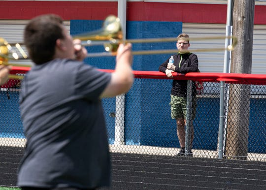 James Lemley watches the band as it practices on the turf of the Zane Trace football field Wednesday. Lemley, who plays and enjoys music, does not participate in the marching band routines.
